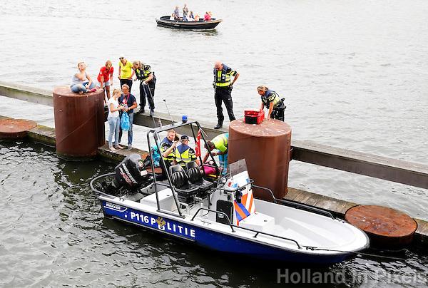 Nederland Amsterdam.  De Waterpolitie verleent hulp aan een persoon, die gewond is geraakt bij het afmeren van zijn boot