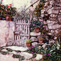 Oppede's charm abounds. The garden gate welcomes visitors. Pots of geraniums cling to stone shelves in this ancient stone wall. After being abandoned in the 17th Oppede has gained new life.<br />