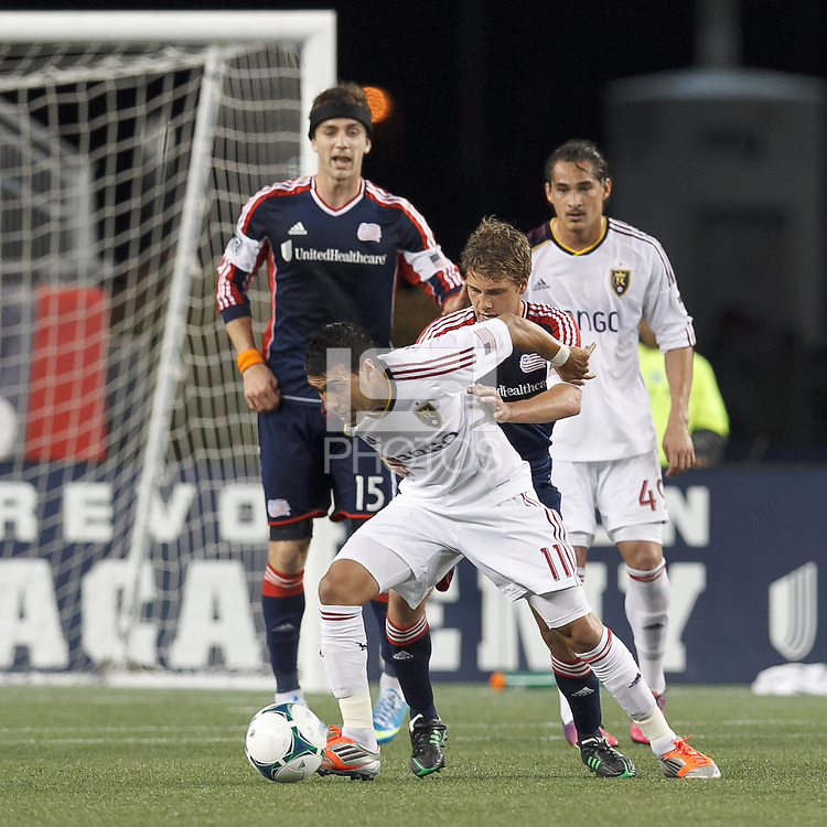 Real Salt Lake midfielder Javier Morales (11) dribbles as New England Revolution midfielder Scott Caldwell (6) closely defends. In a Major League Soccer (MLS) match, Real Salt Lake (white)defeated the New England Revolution (blue), 2-1, at Gillette Stadium on May 8, 2013.