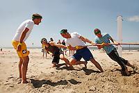 Teambuilding tijdens een personeelsdag op het strand. Touwtrekken