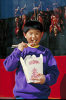 CHINESE-AMERICAN BOY EATING ROAST DUCK TAKE-AWAY WITH CHOPSTICKS OUTSIDE STORE. BOY EATING TAKEOUT CHINESE FOOD. SAN FRANCISCO CALIFORNIA USA.
