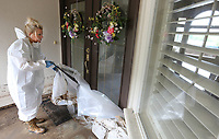 NWA Democrat-Gazette/DAVID GOTTSCHALK Tammy Morse, the daughter of Don and Pat Faubus, pulls Tuesday, June 4, 2019, plastic away from the front door of her parents home on Riverview Drive in Fort Smith. Tuesday was the first opportunity the family had to see the home following the flooding by the Arkansas River.