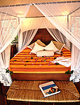 A bed at the Ti Kaye Village, Resort & Spa, an exotic beachside resort and scuba diving near Anse Cochon, St. Lucia in the Caribbean.