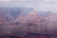 The very tip of Vishnu Temple is lit by a thin ray of light during a November storm over the Grand Canyon.  Seen from the Grandview Trail, below the South Rim.