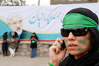 A female supporter of former prime minister Mir-Hossein Mousavi on her mobile phone outside a rally at Heravi stadium before the 2009 presidential election.