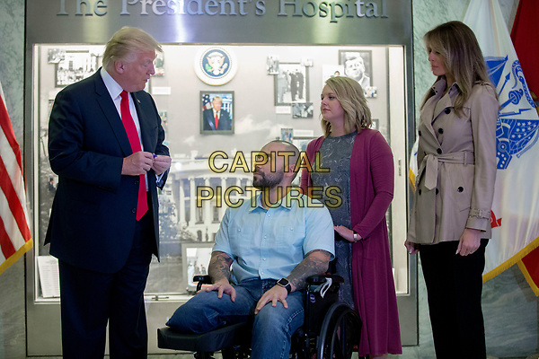 US President Donald J. Trump (L), with First Lady Melania Trump (R), talks with Sergeant First Class Alvaro Barrientos (2-L), with his wife Tammy Barrientos (2-R), prior to awarding the Purple Heart to him during a visit to Walter Reed National Military Medical Center in Bethesda, Maryland, USA, 22 April 2017. Sergeant First Class Alvaro Barrientos was recently injured in Afghanistan while deployed and for the wounds he sustained, he is receiving the Purple Heart.<br /> CAP/MPI/RS<br /> &copy;RS/MPI/Capital Pictures