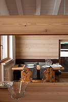 A brown leather banquette and a pair of wooden chairs around a solid wood dining table in the chalet's open-plan living area