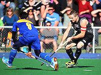 NZ captain Phil Burrows takes on Mohd Madzli Ikmar Mohd Nor during the international hockey match between the New Zealand Black Sticks and Malaysia at Fitzherbert Park, Palmerston North, New Zealand on Sunday, 9 August 2009. Photo: Dave Lintott / lintottphoto.co.nz