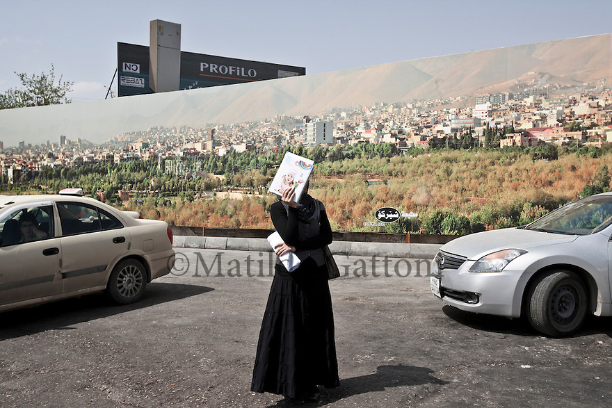 Iraq - Kurdistan - Sulaymaniyah -   Kurd woman waiting for the bus in a parking area
