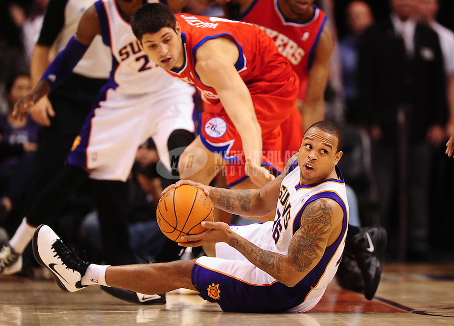 Dec. 28, 2011; Phoenix, AZ, USA; Phoenix Suns guard Shannon Brown on the ground with the ball against Philadelphia 76ers forward Nikola Vucevic at the US Airways Center. The 76ers defeated the Suns 103-83. Mandatory Credit: Mark J. Rebilas-USA TODAY Sports