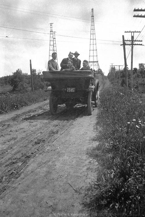Men tour power lines from an open car. Probably near Niagara Falls, New York. Circa 1924