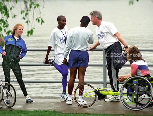 United States President Bill Clinton does some stretching exercises with winners of the Boston Marathon following an early morning jog in Washington, D.C. on April 19, 1995..Credit: Ron Sachs / CNP