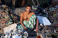 A man sifts through piles of used electronics in a small village near Kolkata.<br /> <br /> To license this image, please contact the National Geographic Creative Collection:<br /> <br /> Image ID: 1925798 <br />  <br /> Email: natgeocreative@ngs.org<br /> <br /> Telephone: 202 857 7537 / Toll Free 800 434 2244<br /> <br /> National Geographic Creative<br /> 1145 17th St NW, Washington DC 20036