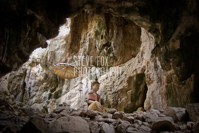 A large Buddha image is illuminated by a hole in the cave  (Khao Yoi) in which it is housed, Phetchaburi, Thailand