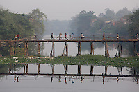 People walk across a bridge above a river on the outskirts of Kolkata.<br />
