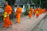 Monks Collecting Alms - the respect given by a lay Buddhist to a Buddhist monk or nun is not charity as presumed by Western eyes but closer to a symbolic connection to the spiritual showing humility and respect.  The presence of so many Buddhist monks is a stabilizing influence in Lao society and the act of alms-giving helps connects lay people to the monk.