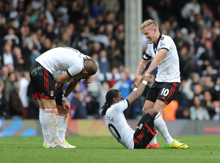 Fulham's Lewis Holtby helps up Hugo Rodallega at the final whistle after their 1-0 victory over Norwich City<br /> <br /> Photo by Ashley Western/CameraSport<br /> <br /> Football - Barclays Premiership - Fulham v Norwich City - Saturday 12th April 2014 - Craven Cottage - London<br /> <br /> &copy; CameraSport - 43 Linden Ave. Countesthorpe. Leicester. England. LE8 5PG - Tel: +44 (0) 116 277 4147 - admin@camerasport.com - www.camerasport.com