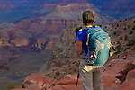 a cross canyon hiker pauses to take in the canyon scenery on the south kaibab trail down in the grand canyon