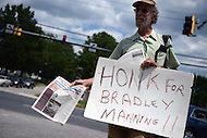 July 30, 2013  (Washington, DC) Dave Shcott, of Baltimore, MD, holds a sign and newspaper supporting Army Private Bradley Manning outside the main gate of Fort Meade after the judge in Manning's trial found him not guilty of aiding the enemy. Manning was found guilty on several other charges.   (Photo by Don Baxter/Media Images International)