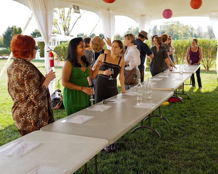 Customers line the bar in an events tent in the side yard at Breaux Vineyards.  A wedding had been held here recently; on this fine weekend the winery decided to serve tastings here to relieve pressure on the indoors tasting bar.
