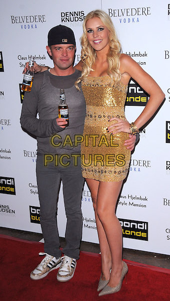 CLAUS HJELMBAK & JAIME WRIGHT .The Bondi Blonde Style Mansion held at The Style Mansion International in Beverly Hills, California, USA..February 9th, 2009.full length gold sequins sequined dress bracelets corona beer hand on hip beige grey gray pointy shoes arm over shoulder top backwards baseball cap hat beverage drink .CAP/DVS.©Debbie VanStory/Capital Pictures.