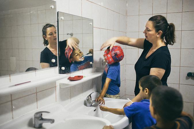 Die Direktorin des Tageszentrums, Natalia Bianca Ursachi putzt einem Kind nach dem Mittagessen die Zaehne. Europa, Rumaenien, Rusciori den 28. Juli 2015