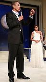 WASHINGTON - JANUARY 20:  (AFP OUT) President Barack Obama speaks to the crowd as his wife Michelle Obama looks on at the Mid-Atlantic Inaugural Ball at the Washington Convention Center on January 20, 2009 in Washington, DC. Obama became the first African-American to be elected to the office of President in the history of the United States.  .Credit: Mark Wilson - Pool via CNP