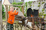 PUFFED OUT:  Young Alex Gyves pumps the old bellows of the forge master's fire at the Kilgarvan Vintage Day and Traditional Music Festival.