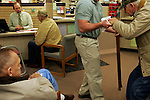 Pharmacist Garrison Moreland of Moreland & Devitt Drugstore in Rushville, Ill., has spent most of the last week explaining to his customers the Medicare changes that will take effect January 1, 2006. Here he counsels Bill Johnson of Astoria, Ill., as pharmacist Rick Bartlett, center, assists customer Merlyn Hunter of Browning, Ill.