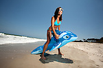 Young Brunette Woman at the beach surfing and enjoying herself