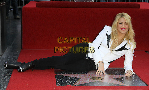 Shakira (Shakira Isabel Mebarak Ripoll) .Shakira is Honored with the a Star on the Hollywood Walk Of Fame Held On Hollywood Blvd., Hollywood, California, USA..November 8th, 2011.full length black jacket blazer white trousers laying lying on side.CAP/ADM/KB.©Kevan Brooks/AdMedia/Capital Pictures.
