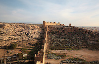 The Jairan Wall in the Hoya ravine, built under King Jairan, 1012-28, and the San Cristobal Hill or Monte Laham, with the statue of statue of the Sacred Heart of Jesus, in the Alcazaba, a 10th century fortified enclosure and royal residence in Almeria, Andalusia, Southern Spain. The Alcazaba itself was begun in 955 by Rahman III and completed by Hayran, Taifa king of Almeria, in the 11th century. It was later added to by the Catholic monarchs. Picture by Manuel Cohen