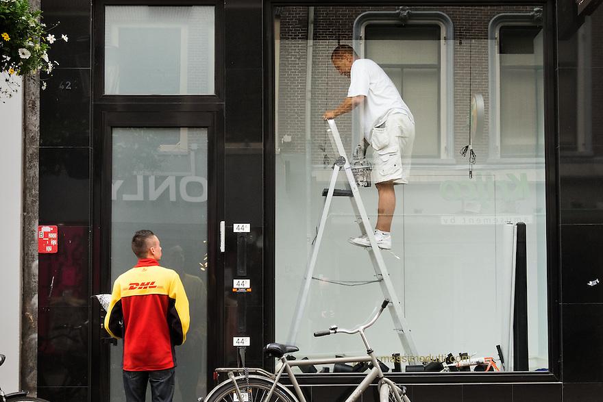 Nederland, Utrecht, 16 juni 2015 <br /> Koerier van DHL belt aan maar er wordt niet opengedaan. De schilder in de etalage naast de deur reageert niet op de koerier, maar de deur geeft ook geen toegang tot de winkel waar de etalage toe behoord. Pakketservices doen goede zaken omdat er veel via internet besteld wordt.<br /> <br /> Foto: Michiel Wijnbergh