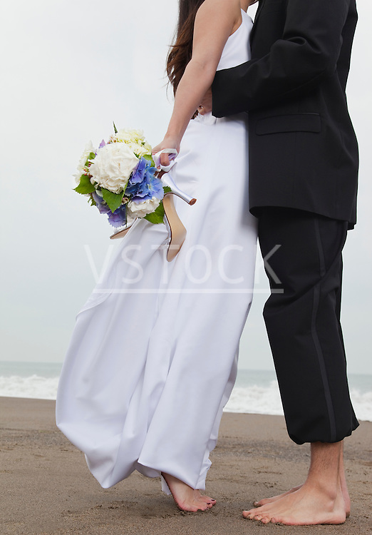 USA, California, San Francisco, Baker Beach, bride and groom walking on beach