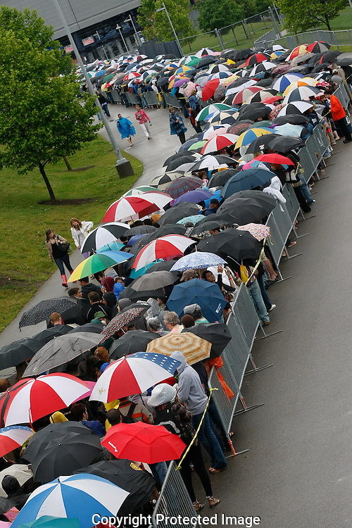 Lines snake up a walkway in the rain at the opening of the American Idol Auditions at Gillette Stadium in Foxboro Mass. on Sunday, June 14, 2009. (Photo by Joe Giblin)