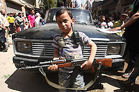 Photographer: Rick Findler..27.04.12 A boy poses with an AK-47 along with a grenade at a rally against President Assad's regime in Armanaz, Northern Syria after Friday prayers this afternoon. The people in Syria still protest against Assad's evil ways, and a ceasefire is far from over after yet another battle in Idlib City today.