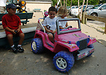 BABYLON, NY-MONDAY, AUGUST 13, 2007: Emma Valle,4, of Babylon, and Justin Alvarez,4 of Deer Park, prepare for a ride in Valle's toy Jeep at Argyle Lake Park in Babylon on Monday August 13, 2007. Looking on at left is another friend, Joseph D'Amato,5, of Deer Park.<br /> Newsday / Jim Peppler