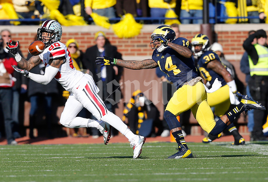 Ohio State Buckeyes wide receiver Chris Fields (80) catches a pass under pressure from Michigan Wolverines safety Josh Furman (14) in the second quarter of the college football game between the Ohio State Buckeyes and the Michigan Wolverines at Michigan Stadium in Ann Arbor, MI Saturday afternoon, November 30, 2013. The Ohio State Buckeyes defeated the Michigan Wolverines 42 - 41. (The Columbus Dispatch / Eamon Queeney)