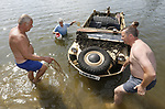 """Foto: VidiPhoto<br /> <br /> ARNHEM – """"Daarom verloren de Duitsers de oorlog"""", grappen omstanders als een nagebouwde Schwimmwagen uit 1994 dinsdag op de Rijn bij Arnhem stilvalt. Terugpeddelen tegen de stroom in is lastig en daarom schieten zwemmers het historische amfibievoertuig te hulp. Een proefvaart van directeur Eef Peeters (blauw shirt) van het Arnhems Oorlogsmuseum 40-45 en collega Rob van Welie met het uit originele onderdelen nagebouwde oorlogstuig, liep dinsdag niet helemaal zoals gepland doordat de koppeling los schoot. Nieuwsgierige strandgasten in de buurt schoten snel te hulp. Peeters kocht het voervaartuig van een particulier die een volkswagen ombouwde tot amfibievoertuig. Omdat de Duitse Wehrmacht en SS in de oorlog een soortgelijk transportmiddel had, wil Peeters het varend voertuig terugbrengen in originele staat. Omdat een originele Schwimmwagen niet alleen peperduur en zeldzaam is, maar ook erg instabiel, wordt er nauwelijks mee gevaren. Het karkas van deze Schwimmwagen is opgevuld met purschuim, en kan daarom niet zinken."""