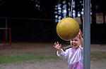 Child reaching for tetherball in playground with excited look on face