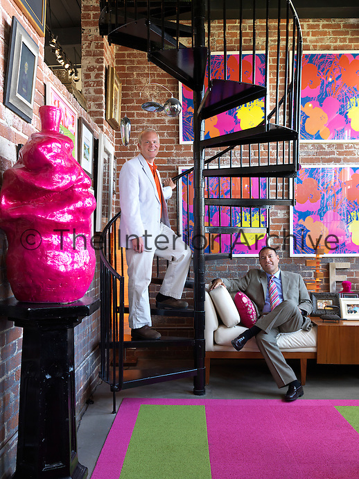 Owners Tripp Evans and Ed Cabral at home in their Providence, Rhode Island loft in front of a colourful collection of Andy Warhol-inspired screenprints exhibited on exposed brick walls