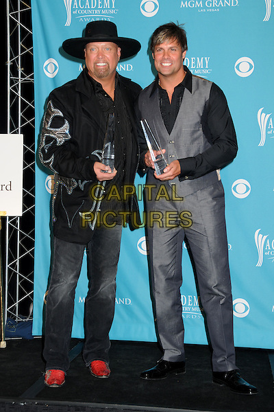 EDDIE MONTGOMERY & TROY GENTRY.45th Annual Academy Of Country Music Awards - Press Room held at the MGM Grand Garden Arena, Las Vegas, Nevada, USA..April 18th, 2010.ACM CMA full length black suit  winner winners trophies hat jeans denim trophy award grey gray .CAP/ADM/BP.©Byron Purvis/AdMedia/Capital Pictures.