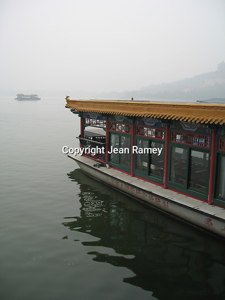 Boats glide through the lake and pollution at the Summer Palace near Beijing, China