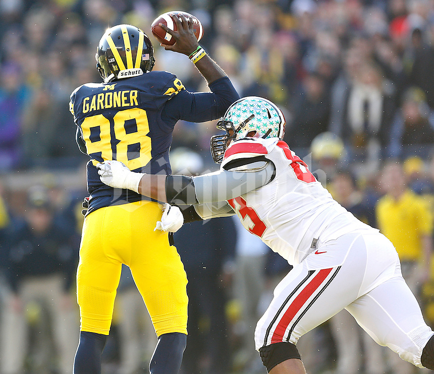 Ohio State Buckeyes defensive lineman Michael Bennett (63) pressures Michigan Wolverines quarterback Devin Gardner (98) in second half action at Michigan Stadium in Ann Arbor, Michigan on November 30, 2013.  (Chris Russell/Dispatch Photo)