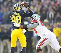 Ohio State Buckeyes defensive lineman Michael Bennett (63) pressures Michigan Wolverines quarterback Devin Gardner (98) in second half action at Michigan Stadium in Ann Arbor, Michigan on November 30, 2013.  (Chris Russell/Dispatch Photo)