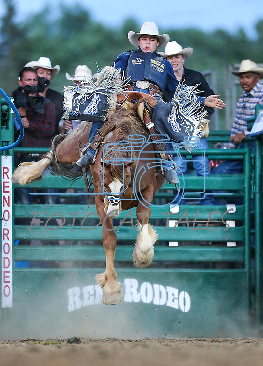 Jesse Wright competes in saddle bronc riding during the Reno Rodeo in Reno, Nev. on Friday, June 19, 2015.<br /> Photo by Cathleen Allison/Nevada Photo Source