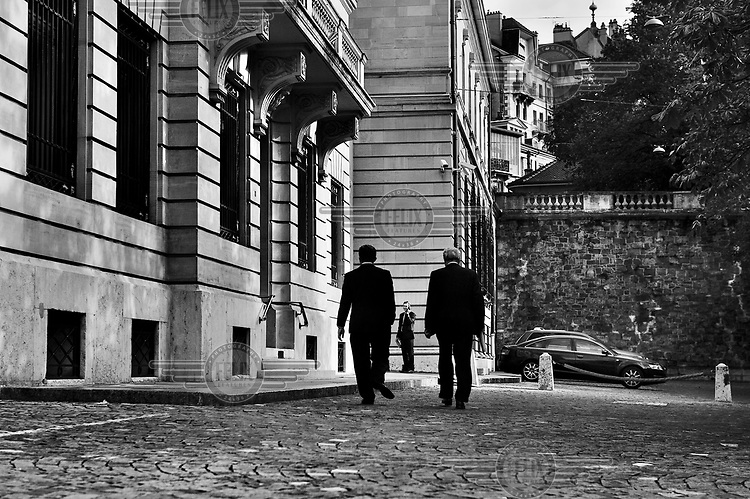 Men walk past the offices of private bank Lombard Odier on the Corraterie, one of the city's principal banking streets.