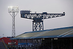 A floodlight and a shipping crane, pictured behind the Shed as Greenock Morton take on Stranraer in a Scottish League One match at Cappielow Park, Greenock. The match was between the top two teams in Scotland's third tier, with Morton winning by two goals to nil. The attendance was 1,921, above average for Morton's games during the 2014-15 season so far.