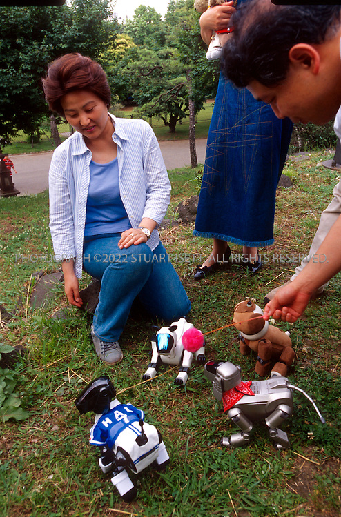 11/15/2002--Tokyo, Japan..Owners of Sony AIBO robot dogs paly with their 'pets' in a park in central Tokyo...All photographs ©2003 Stuart Isett.All rights reserved.This image may not be reproduced without expressed written permission from Stuart Isett.