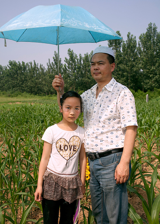 China / Henan Province / Luoyang / Mapo village / 28.6.2013 / Sufeiya and her father,  Ding Shixiao, pose for a portrait during the 36th anniversary of the death of the great-grandfather of Ding Lan.<br />